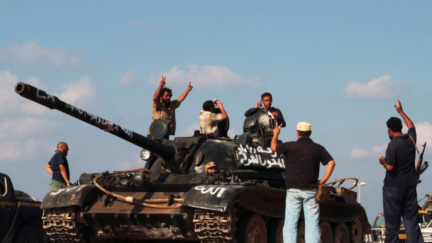 Sept. 17: Revolutionary fighters ride a tank as they celebrate on their way back from the front line in Sirte, Libya.