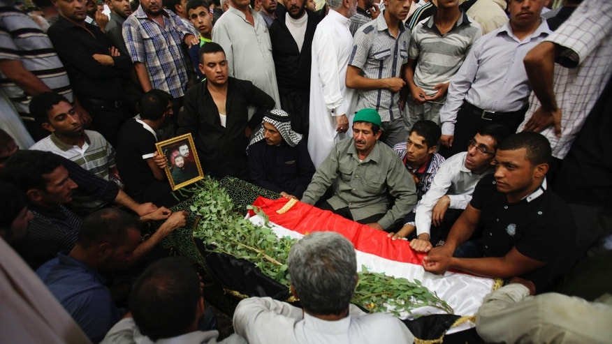 Mourners pray over the coffin a slain Shiite pilgrim during his funeral in the holy city of Karbala, 80 kilometers (50 miles) south of Baghdad, Iraq, Tuesday, Sept. 13, 2011.