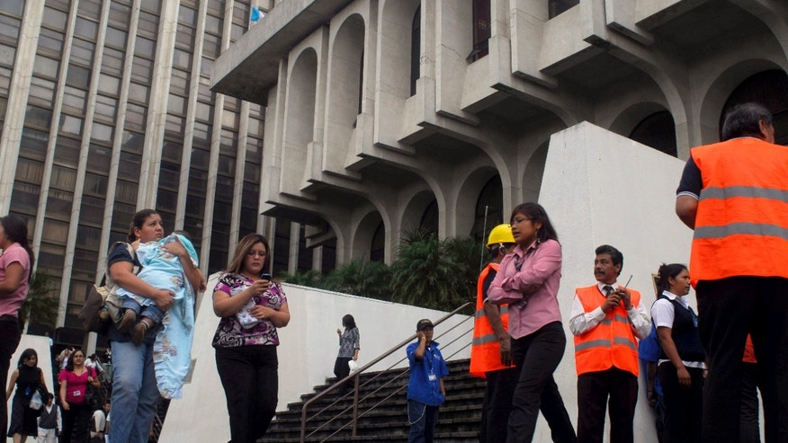 September 19: Residents stand outside the Supreme Court headquarters as volunteer workers organize an evacuation after earthquakes in Guatemala City.