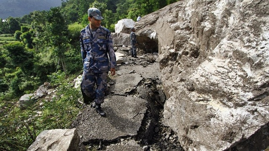 Sept. 21: Nepalese police personnel pass by the damaged portion of the Dharan-Dhankuta road about 133 miles from Katmandu, Nepal.