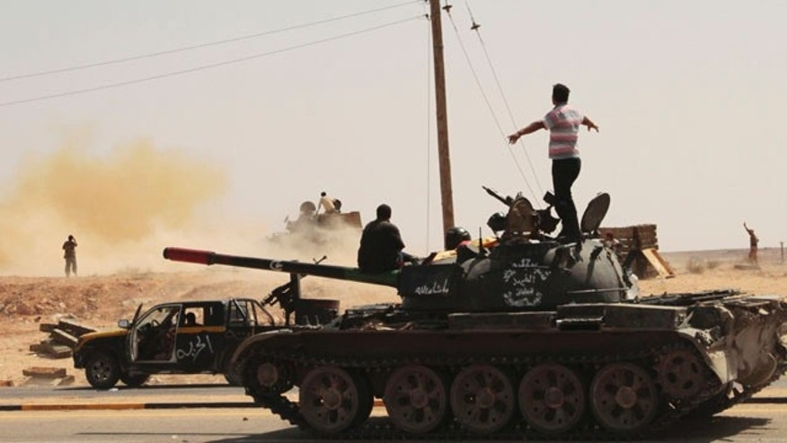 Sept. 25: Revolutionary fighters fire a tank towards a Qaddafi loyalist sniper position in Sirte, Libya.