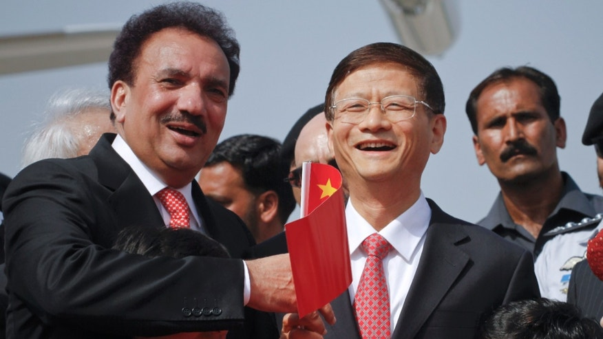 September 26: Chinese Public Security Minister Meng Jianzhu, second right, and Pakistani Interior Minister Rehman Malik, left, wave a Chinese flag upon Jianzhu's arrival at Chaklala airbase in Rawalpindi, Pakistan.