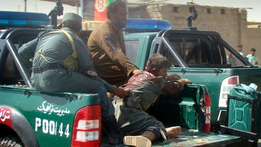 Sept. 27: An injured Afghan police officer is transported on the back of a vehicle after a suicide attack in Lashkar Gah, Helmand province, Afghanistan.