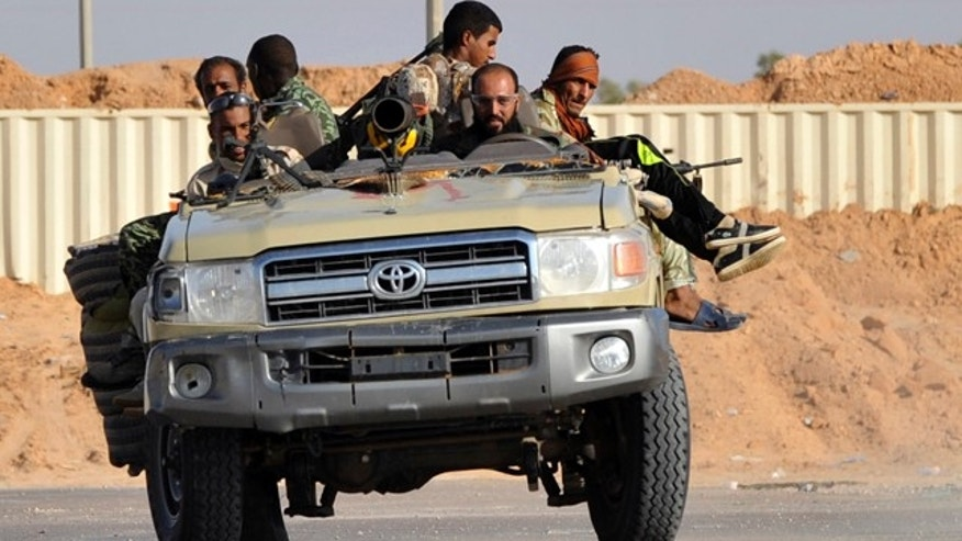 Sept. 27: Libyan revolutionary fighters drive their off-road truck outside Sirte, Libya.