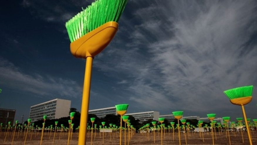 Sep. 28: Brooms planted by protestors stand in front of Brazil's house of Congress in a protest against corruption in Brasilia, Brazil. The 594 green and yellow brooms are the colors of Brazil's flag, and there is one per representative. (AP Photo/Eraldo Peres)