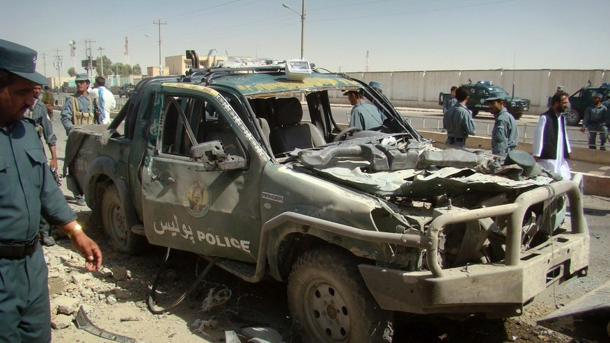 Sept. 27: An Afghan police officer, left, looks at a police vehicle damaged in a suicide attack in Lashkar Gah, Helmand province, Afghanistan. A suicide bomber rammed a car packed with explosives into a police truck outside a bakery in southern Afghanistan on Tuesday, killing a number of civilians, officials said.