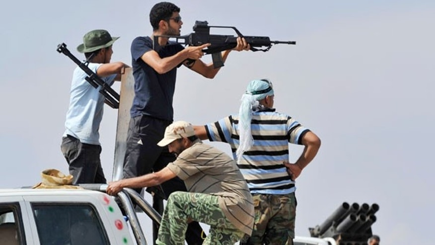 Sept. 30: Libyan revolutionary fighters point at a target during their attack on the city of Sirte, Libya.