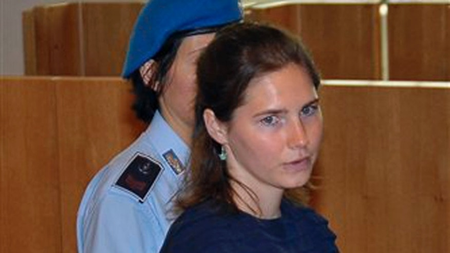 Amanda Knox, escorted by a Penitentiary guard, arrives for the appeal hearing, in Perugia, Italy, Monday, June 27, 2011. The appeals trial of American student Amanda Knox against her murder conviction resumed Monday in a packed courtroom where an Ivorian man convicted in the slaying is to take the stand in closely watched testimony. Rudy Hermann Guede is serving a 16-year-prison sentence for the 2007 murder of Meredith Kercher, a British student who was stabbed to death in the apartment she shared with Knox.