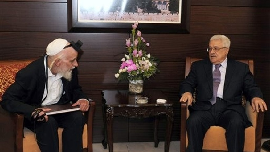In this photo provided by the Palestinian Authority, Aug. 31, 2011, Palestinian President Mahmoud Abbas, right, sits with Israeli settler leader and peace activist Rabbi Menachem Froman during their meeting in the West Bank city of Ramallah.