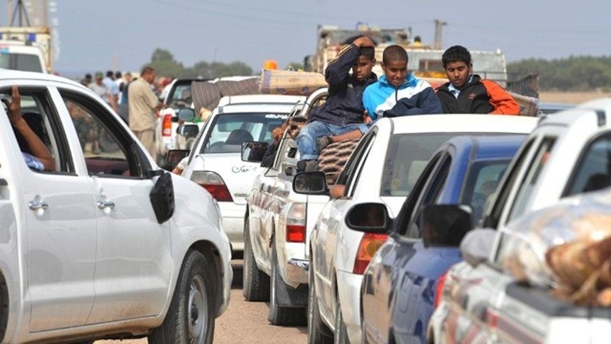 Oct. 2: Internally displaced Libyans flee from the city of Sirte, Libya. Libyan revolutionary fighters stopped battling for the home town of Libya's ousted leader Muammar Qaddafi on Sunday, giving a chance for the civilians to leave the besieged city.