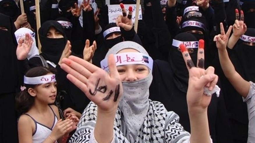 "Sept. 30: In this citizen journalism image made on a mobile phone and provided by Shaam News Network, anti-Syrian President Bashar Assad protesters flash V-victory signs as a woman in the foreground displays her hands with the Arabic word reading: ""leave"", during a demonstration against the Syrian regime, in Edlib province, Syria.  Syrian security forces opened fire on protesters Friday as thousands rallied across the country to call for the downfall of President Bashar Assad's regime, activists said."