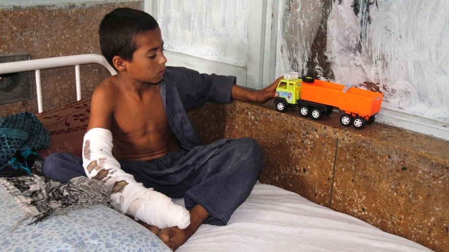 An Afghan boy plays with his toy at a hospital after he was injured by insurgent rocket fire near to the air base of Jalalabad, Afghanistan, Tuesday, Oct. 4, 2011. Two women and three children were injured by the rocket attack, governor spokesman said.