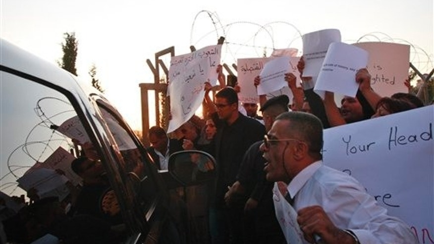 Oct. 4: Palestinians yell at a U.S. diplomatic vehicle during protest against U.S. in the West Bank city of Ramallah. Angry Palestinians accosted a top American official Tuesday during a celebratory West Bank visit in honor of Palestinians who graduated from American-funded education programs.