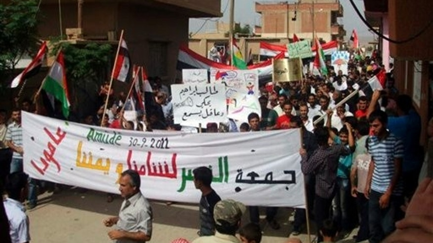 Sept. 30: In this citizen journalism image made on a mobile phone and provided by Shaam News Network, anti-Syrian President Bashar Assad protesters march during a demonstration against the Syrian regime, at the Kurdish-Syrian village of Amouda, in Kamishli province.