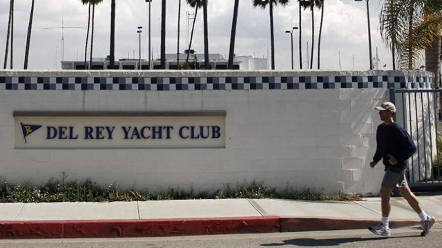 FILE 2011: A man jogs past the Del Rey Yacht Club where Jean and Scott Adams, two of the four Americans killed by Somali pirates, were members in Marina Del Rey, Calif.