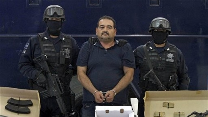 "October 5: Martin Rosales Magana, aka ""El Terry"" an alleged leader of the Mexican La Familia drug cartel, is escorted by police officers during his presentation to the media in Mexico City."