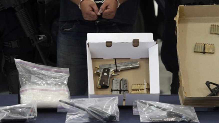 "Martin Rosales Magana, alias  ""El Terry,"" is shown handcuffed to the press, along with arms allegedly seized from him, in Mexico City, Wednesday Oct. 5, 2011.  Authorities allege Rosales is one of the last major leaders of the La Familia cartel, a pseudo-religious drug gang that has been decimated by arrests and killings. Rosales was arrested on Tuesday in the state of Mexico.  (AP Photo/Leonardo Casas)"