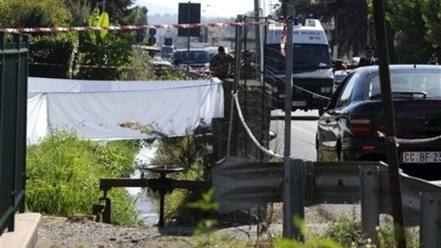 Oct. 5: Police cars are parked along the canal where the body of an American was found in San Giovanni Valdarno, central Italy. Police say they have found the body of an American woman missing in Tuscany for three days and believe she was the victim of a hit-and-run driver.