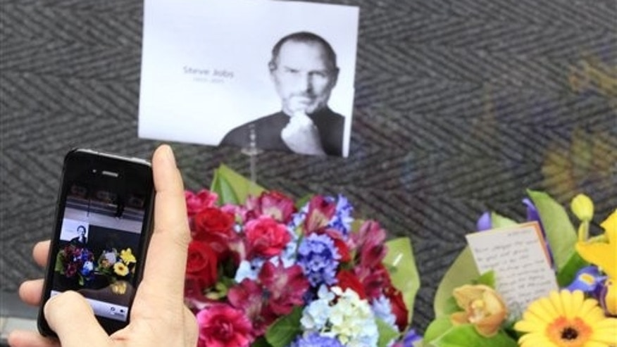 Oct 6: A man uses his iPhone to photograph flowers and a photocopy image of Steve Jobs that is placed at the entrance at the Apple Store in Sydney. Thursday, Oct. 6, 2011.