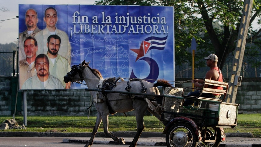 "A driver guides his horse drawn carriage past a billboard demanding the freedom of five Cuban intelligence agents imprisoned in U.S., popularly known as the ""Cuban Five,"" in Havana, Cuba."