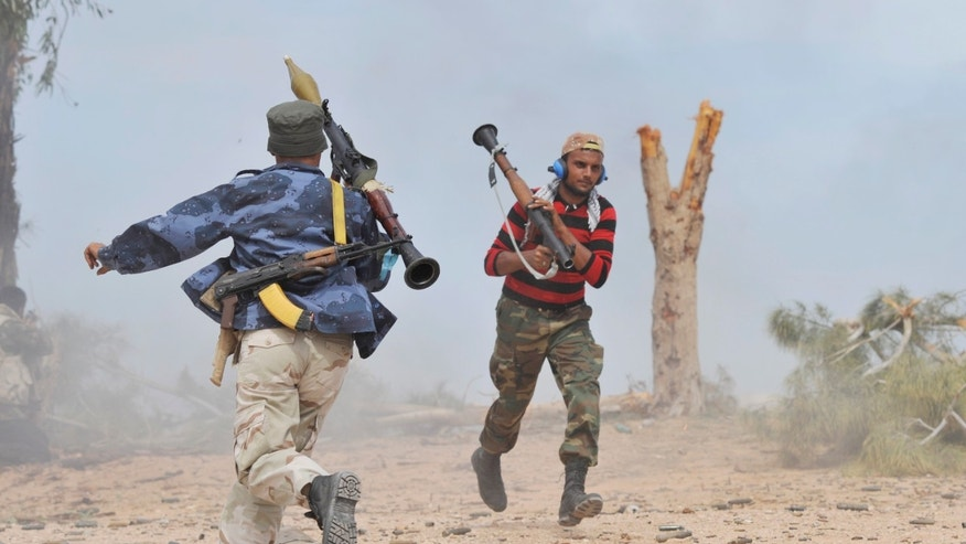 Libyan revolutionary fighters exchange RPG firing positions, while attacking pro-Qaddafi forces inside the Ouagadougou conference center of Sirte, Libya, Friday, Oct. 7, 2011.