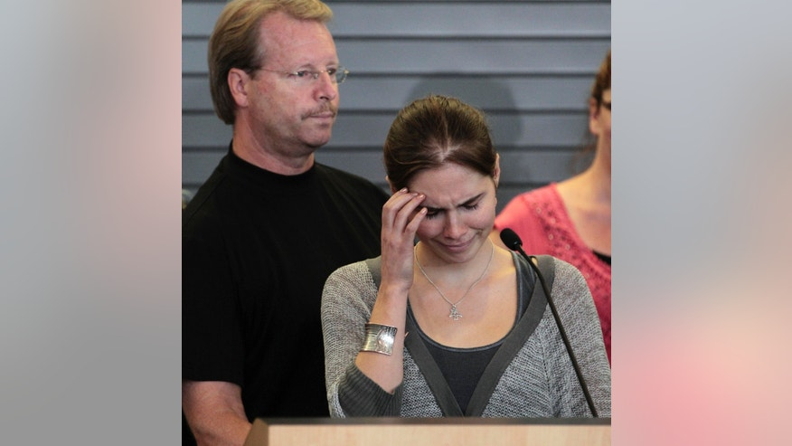 Oct. 4, 2011: Amanda Knox tries to gain her composure to make a statement to the media as her father, Curt Knox, stands behind, shortly after her arrival at Seattle-Tacoma International Airport in Seattle. Knox was freed on October 3 after an Italian appeals court acquitted her on murder charges after four years in prison. Curt Knox says Amanda would like to go back to her university and finish her degree, but that he worries about what the time in prison has done to his 24-year-old daughter.