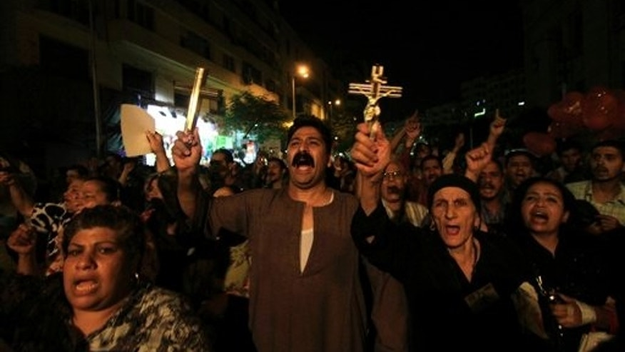 Oct. 4: In this file photo, Egyptian Copts hold Christian crosses and chant slogans as they demonstrate against the sectarian violence, in downtown Cairo, Egypt.  In the past few weeks, riots have broken out at two churches in southern Egypt, prompted by Muslim crowds angered by rumors that Christians were building new churches.