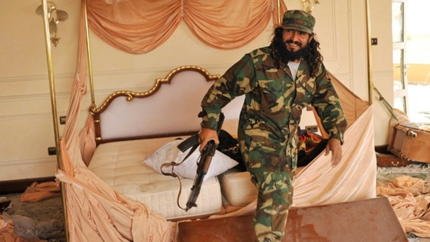 Oct. 10: A Libyan rebel jumps out from the bed of his country's ousted leader Muammar Qaddafi in a palace in Sirte, Libya.