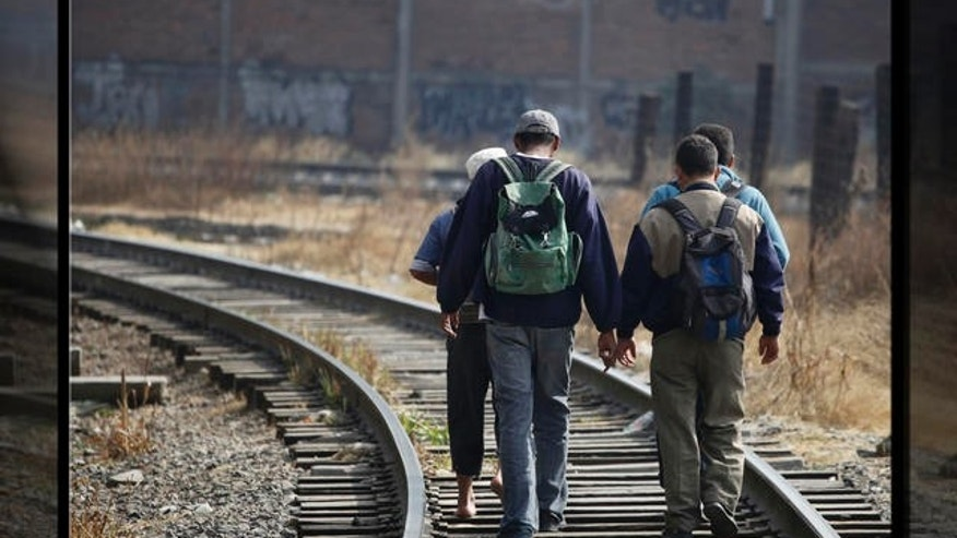 2010: Central American migrants walk along the train tracks as they make their way north on the outskirts of Mexico City.