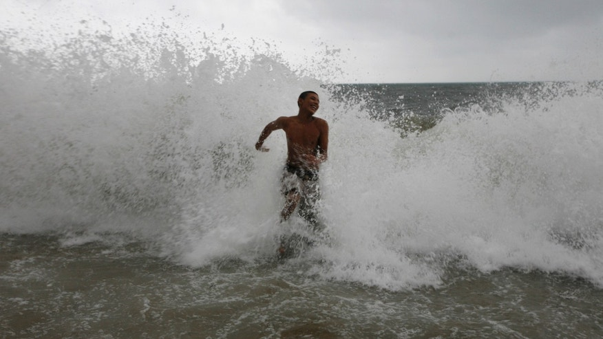 A young man is splashed by a wave while swimming in the waters of Puerto Vallarta, Mexico, Monday Oct. 10, 2011. Hurricane Jova strengthened to a major, Category 3 hurricane Monday as it marched toward Mexico's Pacific coast. (AP Photo/Marco Ugarte)