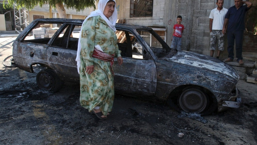 A Palestinian woman walks next to a burnt car in the village of Beit Furik, near the West Bank town of Nablus, Thursday, Sept. 15, 2011.