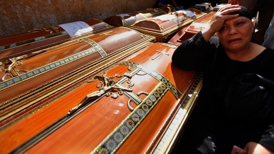 An Egyptian relative of one of the Copts killed during clashes with the Egyptian army late Sunday, mourns over his coffin outside the morgue of the Copts hospital in Cairo, Egypt, Monday, Oct. 10, 2011.