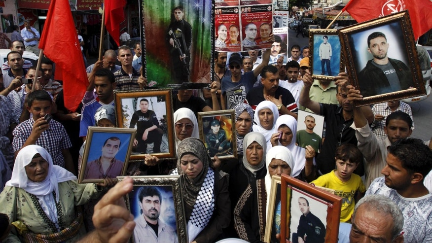 Palestinians demonstrate in solidarity with prisoners jailed in Israel in the West Bank city of Jenin, Thursday, Oct. 13, 2011.