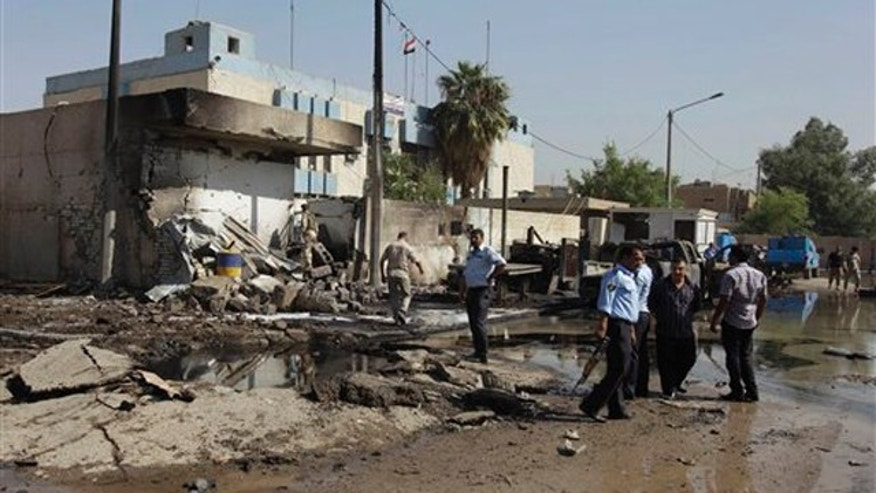 Iraqi security forces inspect a crater caused by a car bomb attack in front of a police station in Baghdad, Iraq, Wednesday, Oct. 12, 2011. A slew of bombings targeting Iraqi police in Baghdad on Wednesday morning killed 12 people and wounded more than 20, Iraqi officials said.