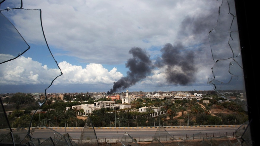 Smoke rises over downtown Sirte, Libya, during fighting between revolutionary fighters and Qaddafi loyalists Thursday, Oct. 13, 2011.