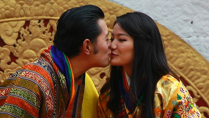 Bhutan's King Jigme Khesar Namgyal Wangchuck, left, and Queen Jetsun Pema kiss in front of the crowd at the main stadium as part of their wedding celebrations in Thimphu, Bhutan, Saturday, Oct. 15, 2011.