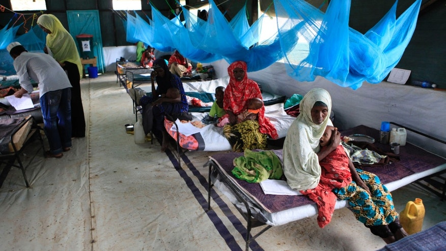 July 11, 201: Somali parents care for their young children who are being treated for malnutrition at a Doctors Without Borders (Medecins Sans Frontieres) hospital in Dagahaley Camp, Dadaab, Kenya.