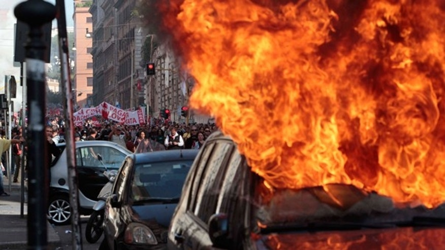 Oct. 15: A car is set on fire as protesters clash with police in Rome. Protesters smashed shop windows and torched cars as violence broke out during a demonstration in the Italian capital, part of worldwide protests against corporate greed and austerity measures.