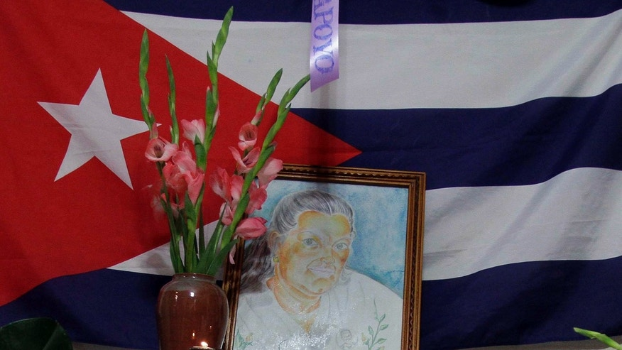 "A painting of Laura Pollan, late leader of the dissident group ""Ladies in White,"" is flanked by flowers, candles and a Cuban flag during a gathering in her honor at her home in Havana, Cuba, Saturday Oct. 15, 2011. According to Elizardo Sanchez, head of the Cuban Commission for Human Rights and National Reconciliation, Pollan died of a cardio-respiratory attack on Friday Oct. 14, 2011. (AP Photo/Franklin Reyes)"