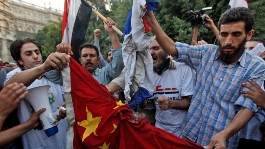 Syrian protesters burn the national flags of China and Russia during an anti-Syrian regime protest in front of the Arab league headquarters in Cairo, Egypt Sunday, Oct. 16, 2011.