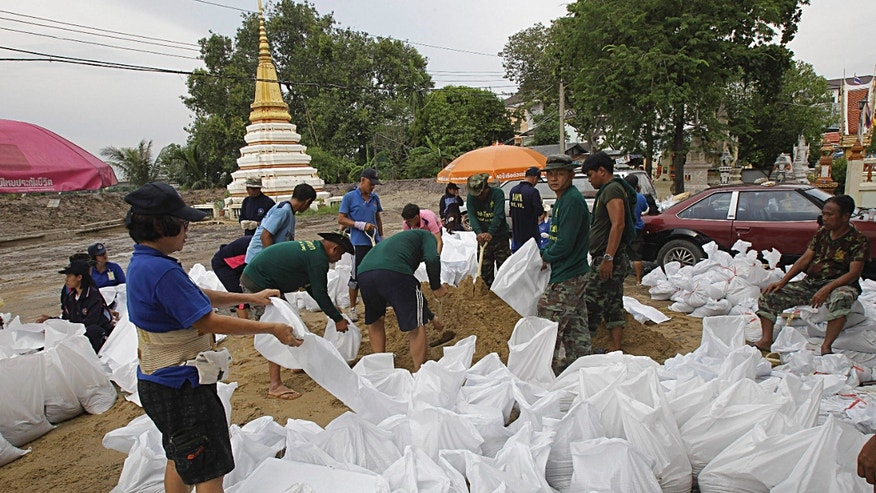 Villagers and soldiers join hands in making sand bags for barricades at a temple in Pak Kred district, Nonthaburi province, Thailand Thursday, Oct. 13, 2011. The ongoing floods is the worst to hit the Southeast Asian nation in decades. About 8.2 million people in 60 of Thailand's 77 provinces have been affected by floods and mudslides, and 30 provinces are currently inundated.