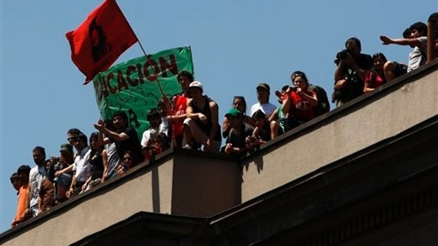 October 19: Students watch demonstrations from the top of a university building in Santiago, Chile.
