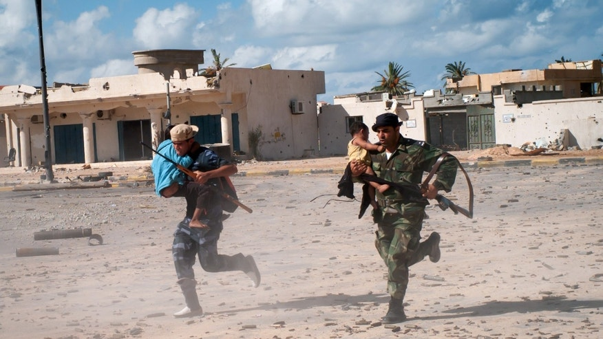Oct. 17, 2011: Revolutionary fighters run across the street under heavy sniper fire carrying Bangladeshi children who were trapped in Sirte, Libya, during the entire siege of the city.