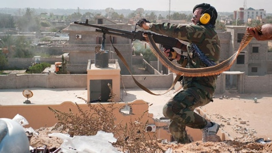 Oct. 18, 2011: A revolutionary fighter fires a belt- fed machine gun under heavy sniper fire on the western front line in Sirte, Libya.