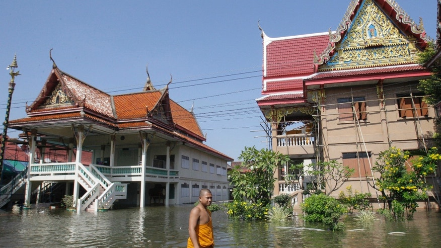Oct. 19, 2011: Thai Buddhist monk wades through a flooded street at Ban Kadee temple in Phatum Thani province, north of Bangkok ,Thailand.