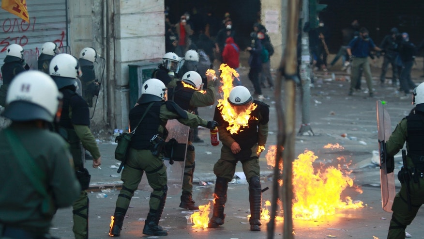 October 20: A Greek riot policeman tries to extinguish a fire after his colleague caught fire from a petrol bomb thrown by protesters during clashes in central Athens.