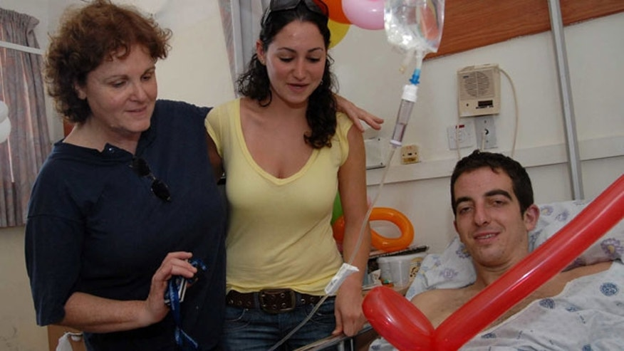 In this photo taken on Aug. 3, 2006, Israeli, U.S-born, Ilan Grapel, right, pauses for a photographer as he is hospitalized after he was injured during the Israel Lebanon war at the Rambam hospital in the northern Israeli city of Haifa.
