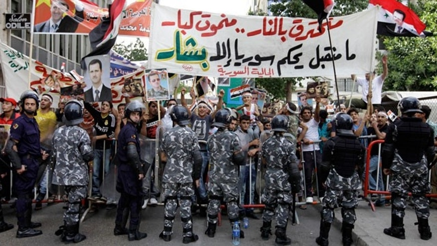 Oct. 23, 2011: Lebanese riot police officers stand guard between supporters and opponents of Syrian President Bashar Assad's regime, during a protest in front of the Syrian embassy, in Beirut, Lebanon.
