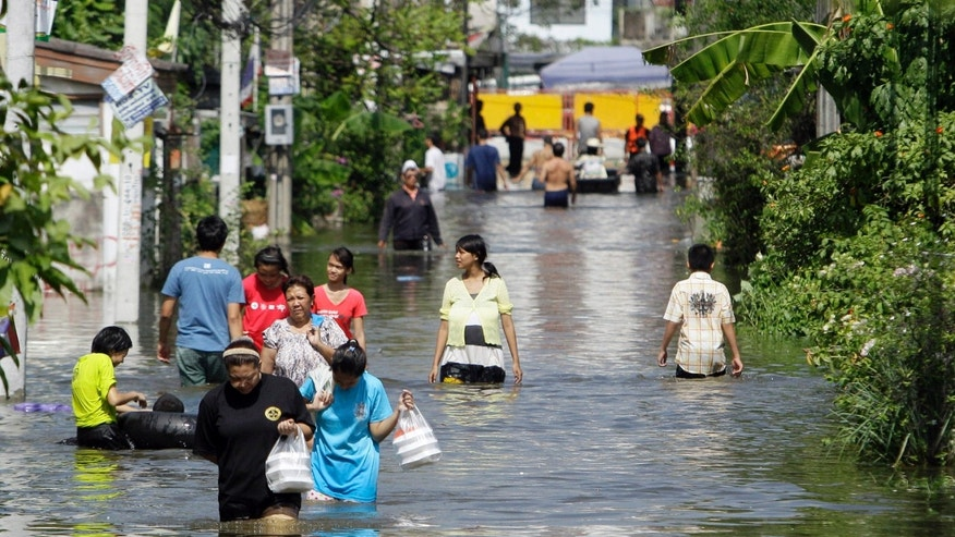 Oct. 25, 2011: People wade through floodwaters in Bangkok, Thailand.