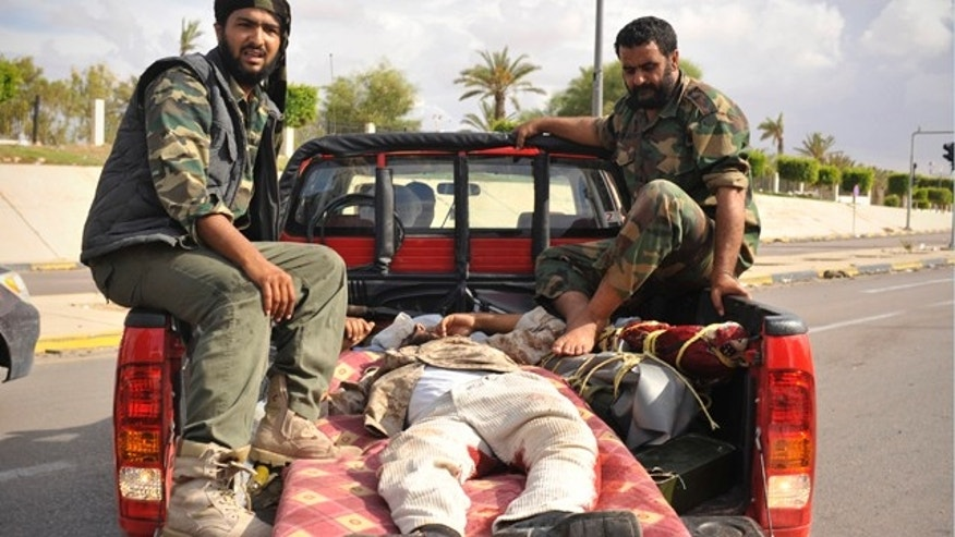 Oct. 13: Libyan revolutionary fighters transport their injured comrade in Sirte, Libya.